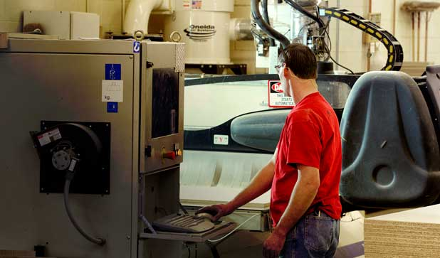 A CNC operator standing next to an industrial CNC machine